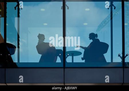 Deux femmes parlant lors d'une pause dans la journée de travail sont vus assis et qui se profile derrière le verre Banque D'Images