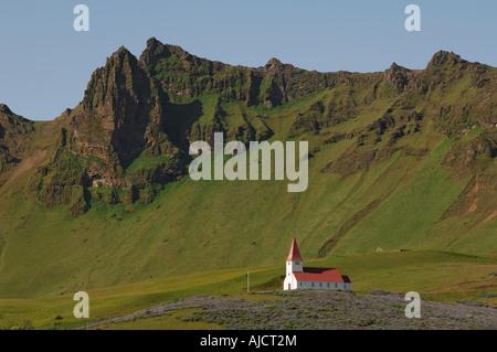 L'église rouge et blanc entouré de champs de lupins, sur une colline au-dessus de la ville de Vik l'Islande du sud Banque D'Images