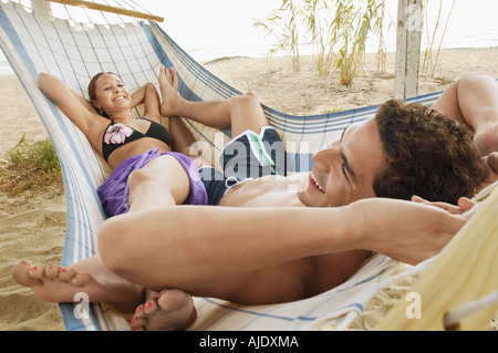 Heureux Couple in Hammock on Beach Banque D'Images