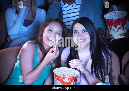 Deux jeunes femmes en cinéma popcorn partage Banque D'Images