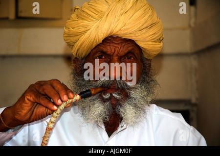Vieil homme au turban jaune fumer le narguilé avec des rides visage merveilleux Banque D'Images