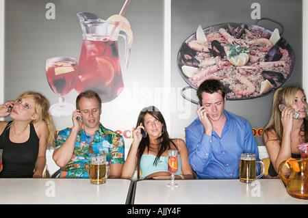 Amis dans un bar sur les téléphones mobiles Banque D'Images