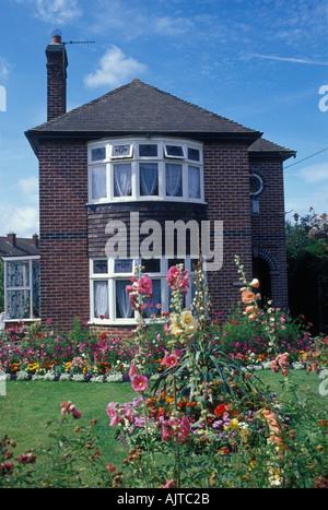 Evercreech Somerset Angleterre Années 20 30s maison individuelle de brique avec des fleurs de jardin pelouse avant Banque D'Images