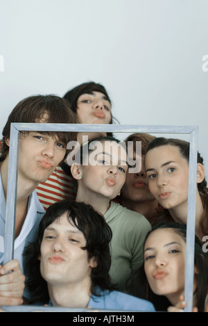 Groupe de jeunes amis qui pose pour photo, holding up photo frame, plissements, portrait Banque D'Images