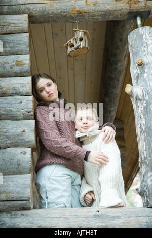 Teen girl embracing petit frère, portrait Banque D'Images