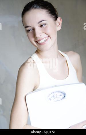 Jeune femme tenant balance de salle, smiling, portrait Banque D'Images