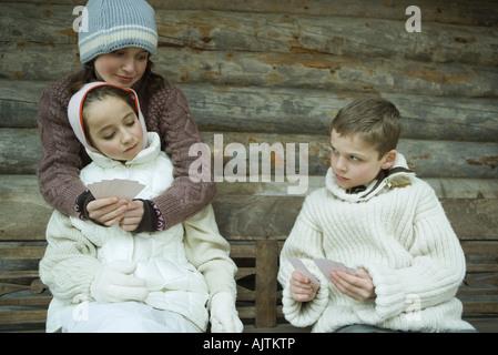 Jeunes amis dans des vêtements d'hiver des cartes à jouer Banque D'Images