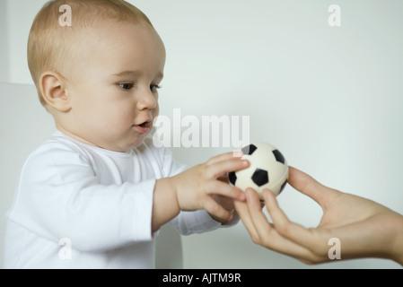 En tenant bébé balle de mother's hand, close-up
