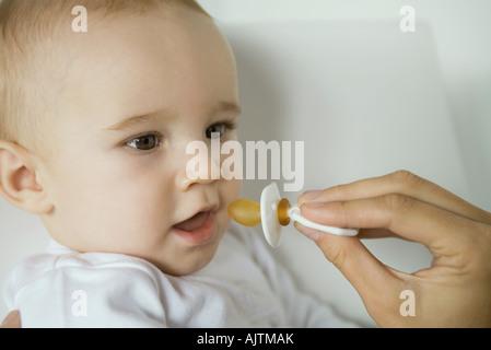 Mother's hand holding up sucette pour bébé