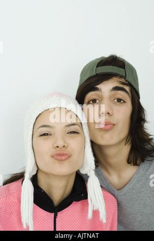 Jeune couple looking at camera, joue contre joue, les plissements, portrait Banque D'Images