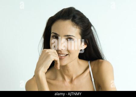 Femme tenant la main près de la bouche, smiling at camera, portrait Banque D'Images