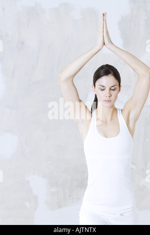 Young woman doing yoga pose, bras levés, les yeux fermés Banque D'Images
