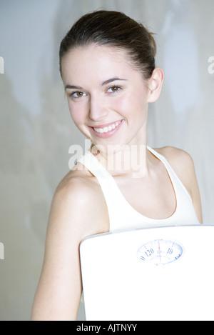 Jeune femme tenant balance de salle, smiling at camera, portrait Banque D'Images