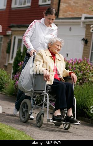 Adolescente poussant et vieille femme dans un fauteuil roulant Banque D'Images