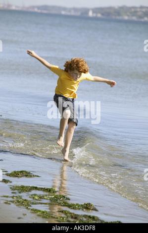 Jeune garçon à l'autre dans l'eau sur une plage Banque D'Images