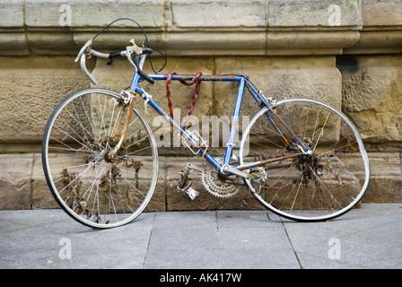 Un vieux vélo de course s'appuie contre un mur de pierre abandonnées dans la vieille ville de San Sebastian, Espagne. Banque D'Images