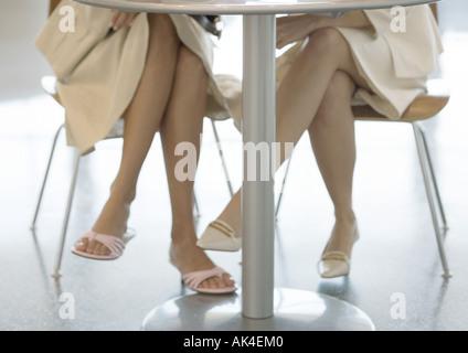 Deux femmes assis à table, la vue de jambes sous la table Banque D'Images