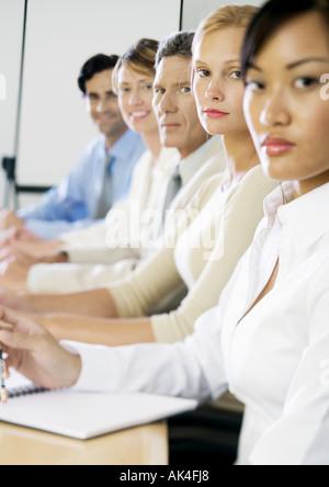 Groupe de dirigeants assis à table en réunion, looking at camera Banque D'Images
