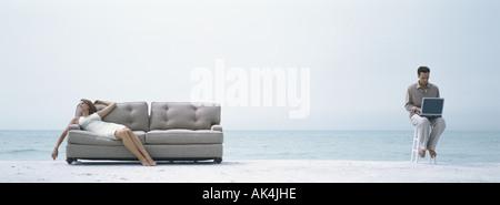 Sur la plage, femme sieste sur canapé tandis que l'homme est assis sur la selle à l'aide d'ordinateur Banque D'Images