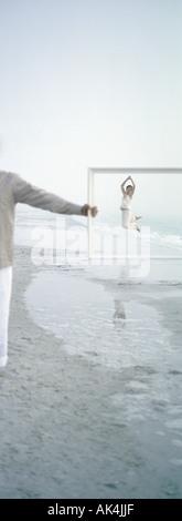 Sur la plage, femme sautant dans la distance, vu à travers le cadre organisé par l'homme Banque D'Images
