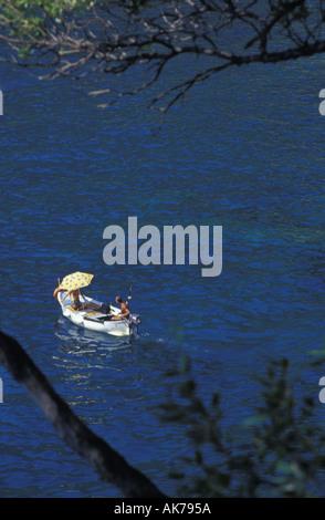 Deux personnes sur un bateau à voile et de la pêche dans un océan bleu près de la côte de la Ligurie en Italie Banque D'Images