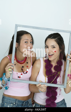 Deux jeunes femmes friends holding up photo frame, smiling at camera, portrait Banque D'Images