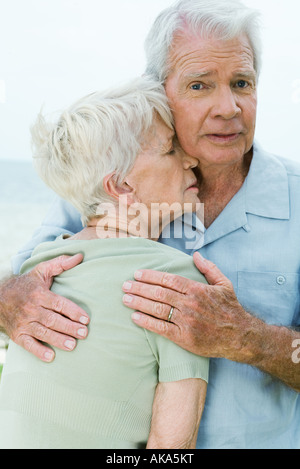 Couple, man holding woman étroitement contre lui, looking at camera Banque D'Images