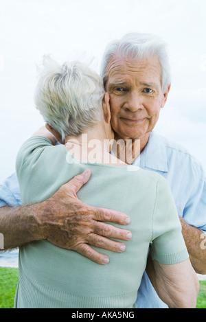 Senior couple hugging, man looking at camera Banque D'Images