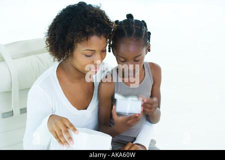 Mère et fille à l'heure actuelle, à la fille assise sur les genoux de femme Banque D'Images