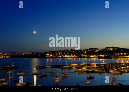Le port de Torquay éclairée par le clair de lune bleu magnifique ciel du soir au crépuscule avec des réflexions Banque D'Images