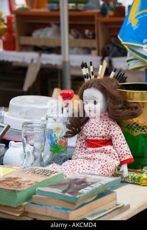 Poupée porcelaine face est assis sur table entre des livres et des bibelots à la rue du marché en plein air à Venise Banque D'Images