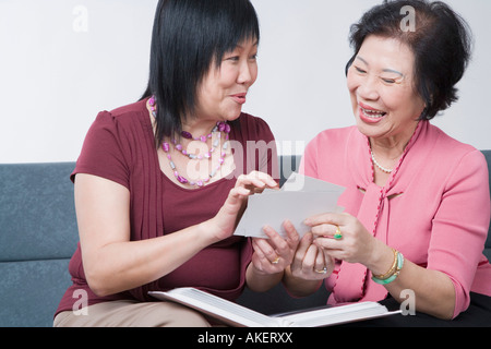 Close-up of a young woman and a Senior woman looking at photographs and smiling Banque D'Images