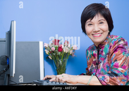 Portrait of a senior woman using a computer and smiling