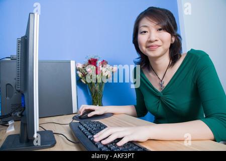 Portrait d'une jeune femme à l'aide d'un ordinateur et un sourire