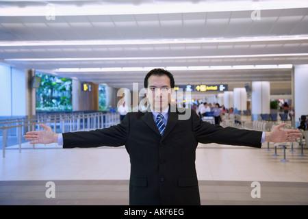 Portrait of a businessman standing dans un bar d'aéroport avec ses bras tendus Banque D'Images
