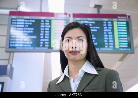 Portrait of a businesswoman in front of an airport departure board Banque D'Images