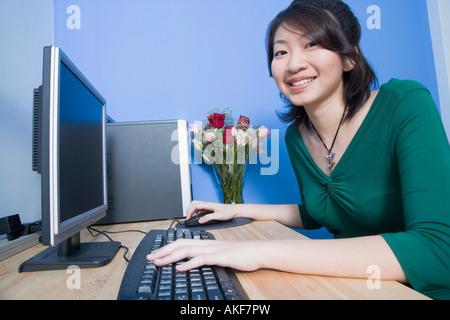 Portrait d'une jeune femme à l'aide d'un ordinateur et souriant