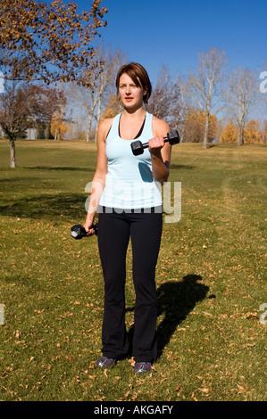 Jeune femme effectuant des biceps Banque D'Images
