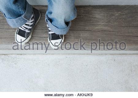 Un enfant portant des jeans et des formateurs Banque D'Images