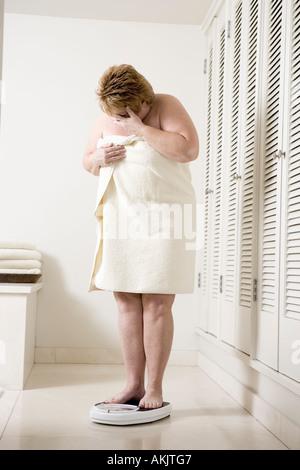 Honte sur l'échelle de bain femme surpoids Banque D'Images