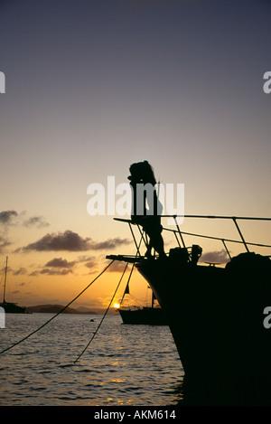 BVI Cooper Island romantic couple on bow de voile au coucher du soleil Banque D'Images