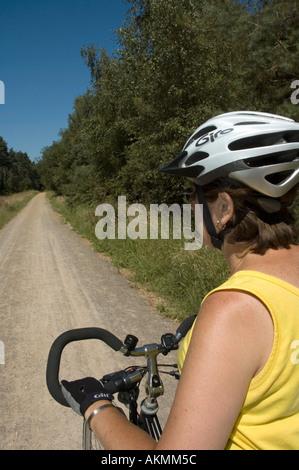 Cycliste féminine sur une piste forestière Banque D'Images