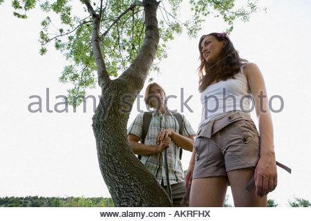 Jeune couple debout près d'un arbre Banque D'Images