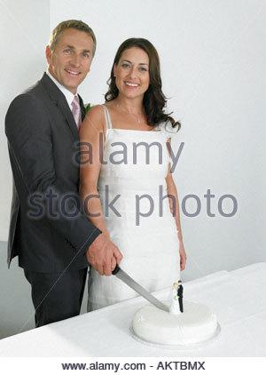 Les nouveaux mariés couper le gâteau de mariage Banque D'Images