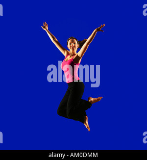 Teenage girl jumping on blue background Banque D'Images
