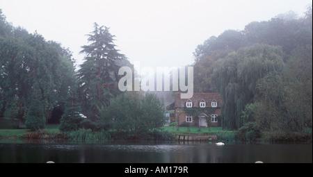 Cottage et arbres matures dans la brume du matin au bord de la rivière Thames nr Whitchurch-on-Thames, en face de Beale Park, Oxfordshire, Angleterre