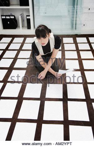 Woman kneeling on floor in office Banque D'Images