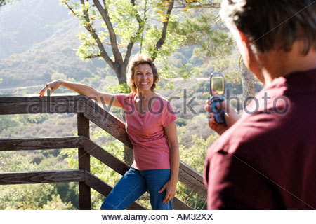 Man taking photo avec téléphone appareil photo de femme sur l'extérieur escalier Banque D'Images