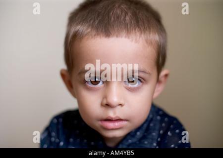 Un garçon de trois ans a l'air en direction de l'appareil photo Banque D'Images