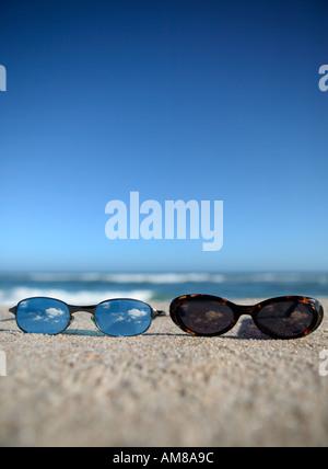 Deux verres portant sur la plage. Banque D'Images